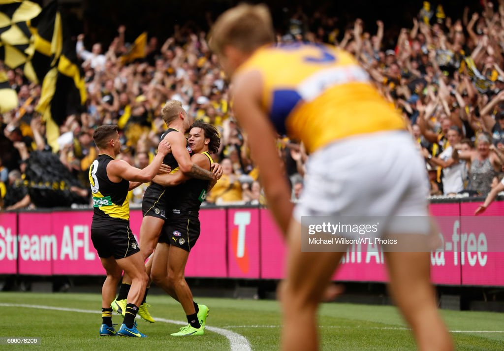 Tigers players celebrate with Daniel Rioli of the Tigers after he goaled from the boundary during the 2017 AFL round 03 match between the Richmond Tigers and the West Coast Eagles at the Melbourne Cricket Ground on April 08, 2017 in Melbourne, Australia.