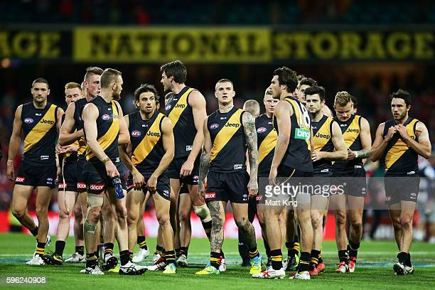 Tigers players look dejected as they leave the field after the round 23 AFL match between the Sydney Swans and the Richmond Tigers at Sydney Cricket...