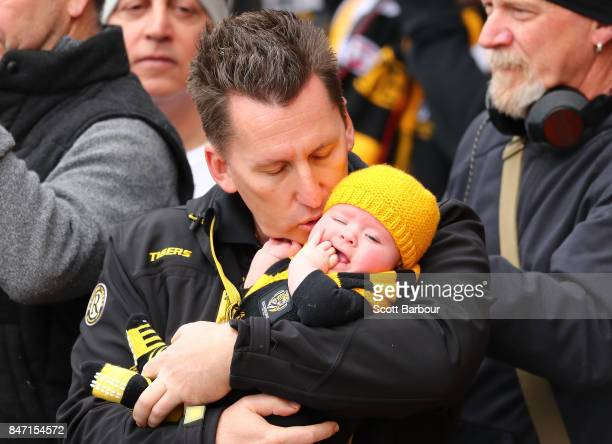 Tigers supporter and his young baby in the crowd watch players train during a Richmond Tigers AFL training session at Punt Road Oval on September 15...
