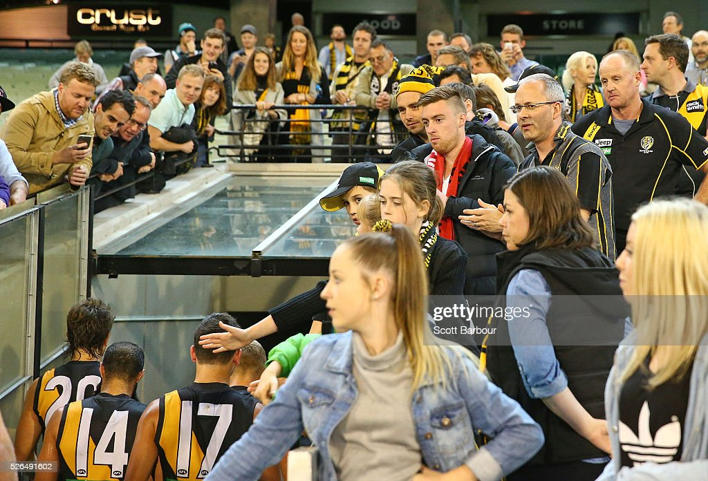 Tigers supporters in the crowd look on as Trent Cotchin and the Tigers leave the field at full time after losing the round six AFL match between the Richmond Tigers and the Port Adelaide Power at Melbourne Cricket Ground on April 30, 2016 in Melbourne, Australia.