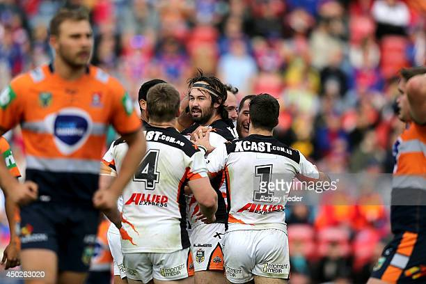 Tigers teammates celebrate a try with Knights players looking dejected in the background during the round 13 NRL match between the Newcastle Knights...