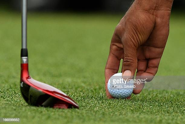 Tigers Woods of the US places his ball to tee off the final round of the 77th Masters golf tournament at Augusta National Golf Club on April 14 2013...