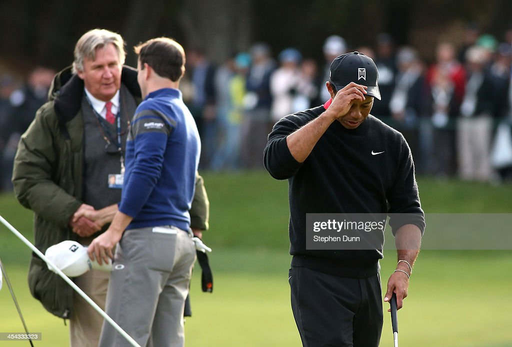 Tigers Woods walks off the green as Zach Johnson is congrtulated by PGA Tour rules official Mark Russell after Johnson defeated Woods on the first playoff hole during the final round of the Northwestern Mutual World Challenge at Sherwood Country Club on December 8, 2013 in Thousand Oaks, California.