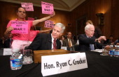 Tighe Barry of Code Pink protests prior to a confirmation hearing before the Senate Foreign Relations Committee for Ambassador Ryan Crocker as he and...
