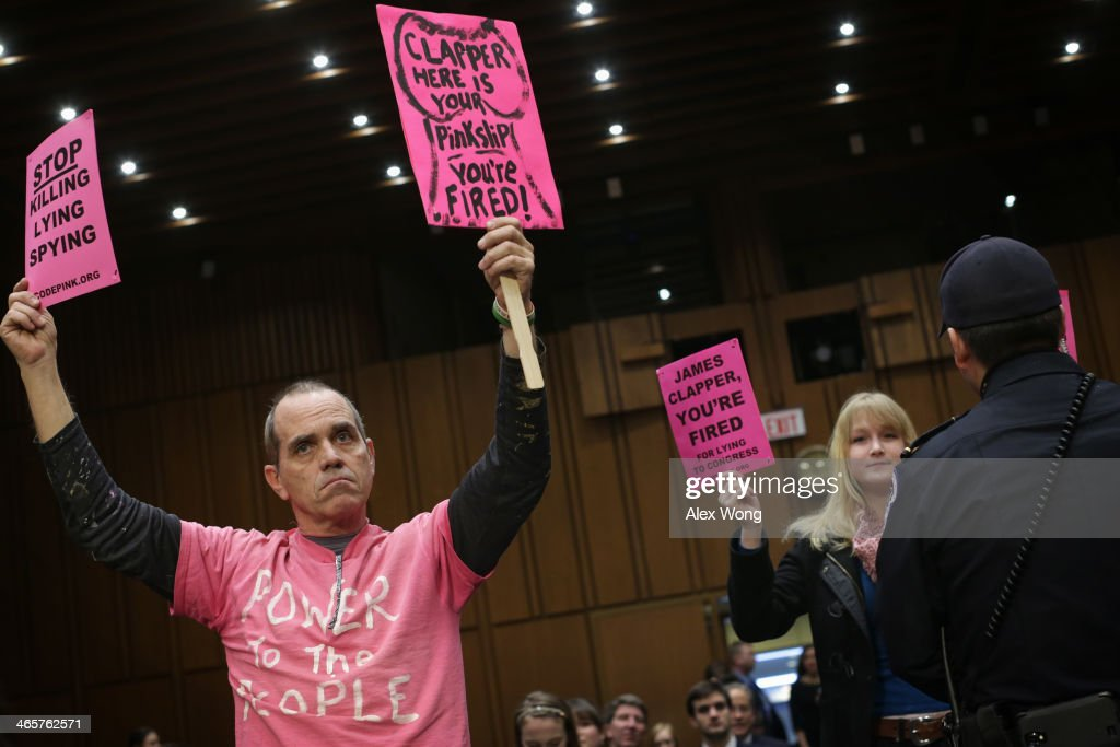 Tighe Barry of CodePink holds signs as he protests prior to a hearing before Senate Intelligence Committee January 29 2014 on Capitol Hill in...