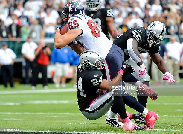 Tighe End Joel Dreesen of the Houston Texans runs over Michael Huff of the Oakland Raiders into the endzone for a touchdown during an NFL football...