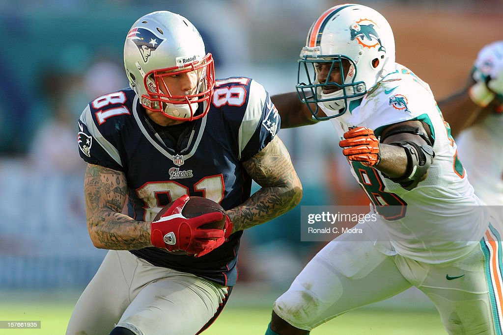 Tight end Aaron Hernandez of the New England Patriots carries the ball after catching a pass during a NFL game against the Miami Dolphins at Sun Life...