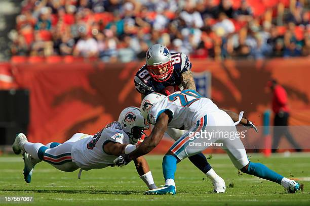 Tight end Aaron Hernandez of the New England Patriots is tackled by free safety Reshad Jones of the Miami Dolphins at Sun Life Stadium on December 2...