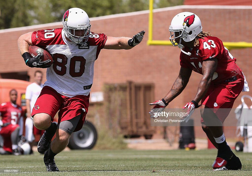 Tight end Alex Gottlieb #80 of the Arizona Cardinals runs with the football against cornerback Ronnie Yell #43 at the team's training center facility on May 10, 2013 in Tempe, Arizona.