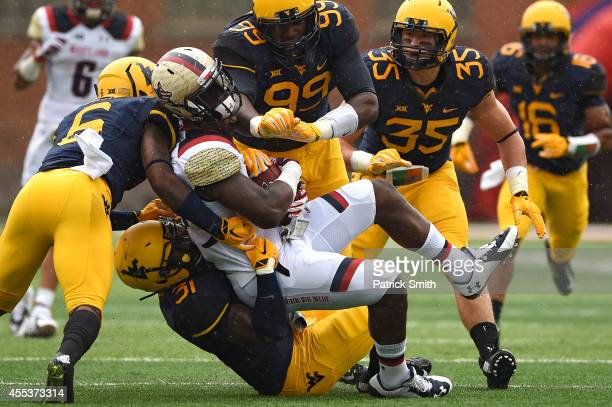 Tight end Andrew Isaacs of the Maryland Terrapins is hit by linebacker Isaiah Bruce of the West Virginia Mountaineers and teammates in the second...