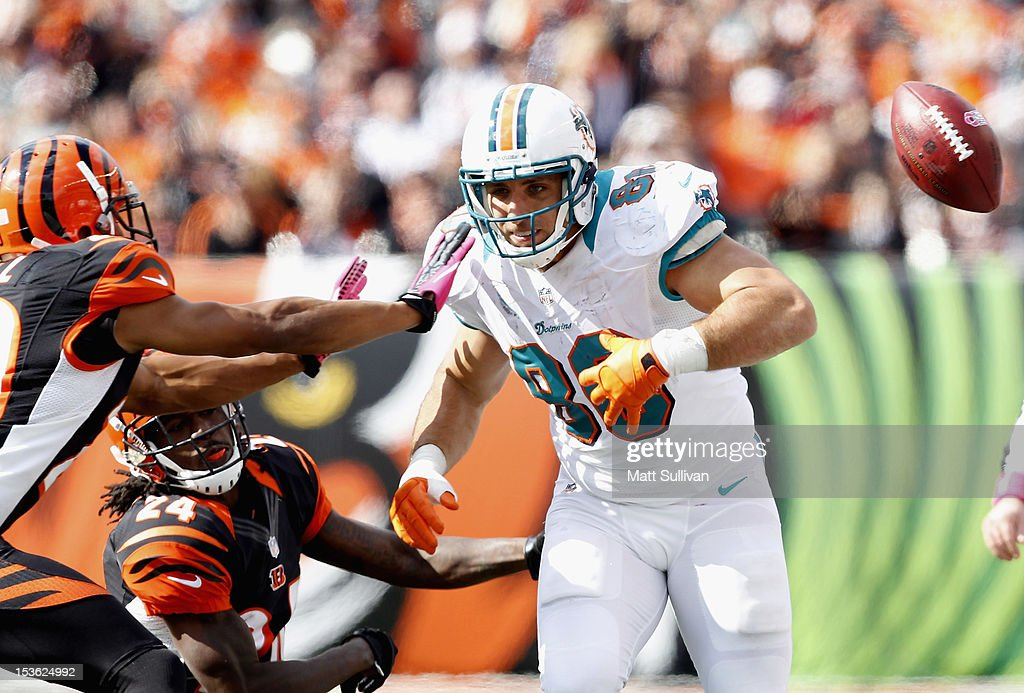 Tight end <a gi-track='captionPersonalityLinkClicked' href=/galleries/search?phrase=Anthony+Fasano&family=editorial&specificpeople=620269 ng-click='$event.stopPropagation()'>Anthony Fasano</a> #80 of the Miami Dolphins fumbles the ball as he is hit by cornerbacks <a gi-track='captionPersonalityLinkClicked' href=/galleries/search?phrase=Leon+Hall&family=editorial&specificpeople=223989 ng-click='$event.stopPropagation()'>Leon Hall</a> #29 and Adam Jones #24 of the Cincinnati Bengals at Paul Brown Stadium on October 7, 2012 in Cincinnati, Ohio.
