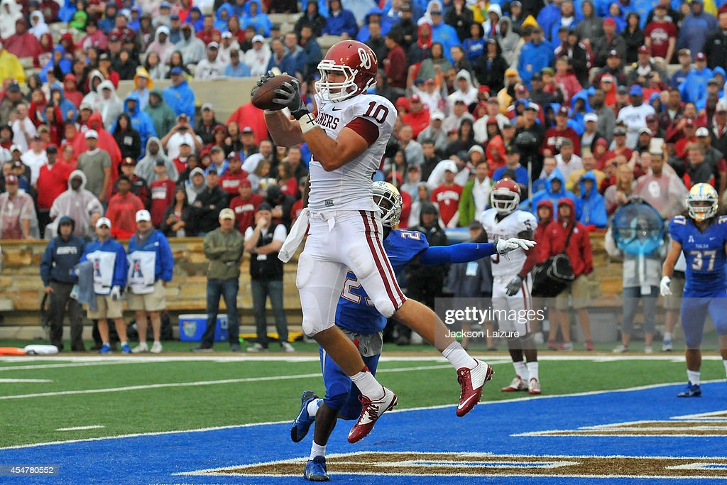 Tight end Blake Bell of the Oklahoma Sooners catches a first half touchdown in front of defensive back Will Barrow of the Tulsa Golden Hurricane on...