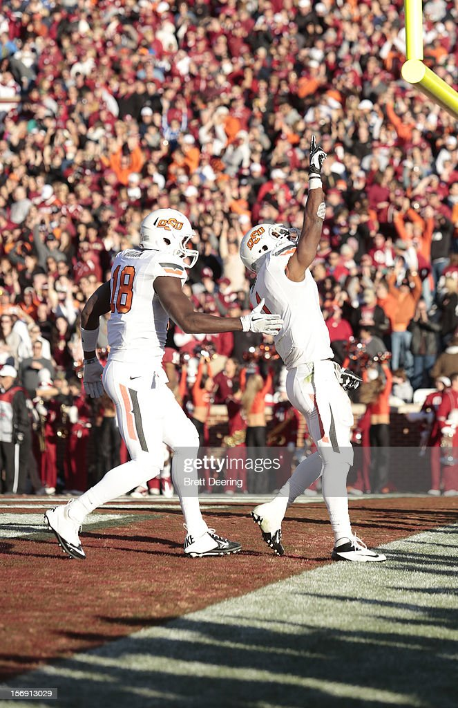 Tight end Blake Jackson #18 and running back Joseph Randle #1 of the Oklahoma State Cowboys celebrate a touchdown against the Oklahoma Sooners November 24, 2012 at Gaylord Family-Oklahoma Memorial Stadium in Norman, Oklahoma. Oklahoma defeated Oklahoma State 51-48 in overtime.