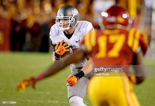 Tight end Blake Jarwin of the Oklahoma State Cowboys drives the ball past defensive back Jomal Wiltz of the Iowa State Cyclones in the second half of...