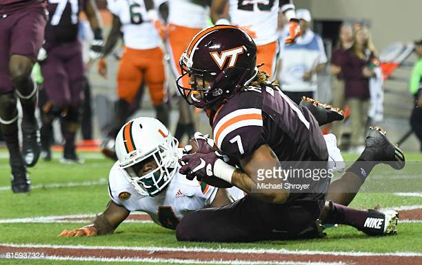 Tight end Bucky Hodges of the Virginia Tech Hokies catches a touchdown pass while being defended by defensive back Jaquan Johnson of the Miami...