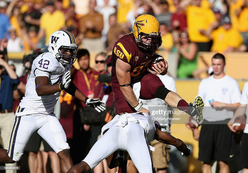 Tight end Chris Coyle #87 of the Arizona State Sun Devils leaps over defensive back Will Shamburger #13 of the Washington Huskies as he runs with the football during the second quarter of the college football game at Sun Devil Stadium on October 19, 2013 in Tempe, Arizona.