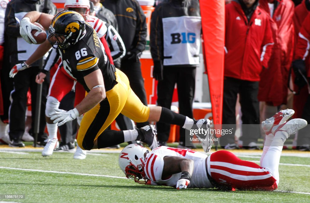 Tight end C.J. Fiedorowicz #86 of the Iowa Hawkeyes is tripped up during the second quarter by linebacker Alonzo Whaley #45 of the Nebraska Cornhuskers on November 23, 2012 at Kinnick Stadium in Iowa City, Iowa. Iowa lead Nebraska 7-3 at the half.