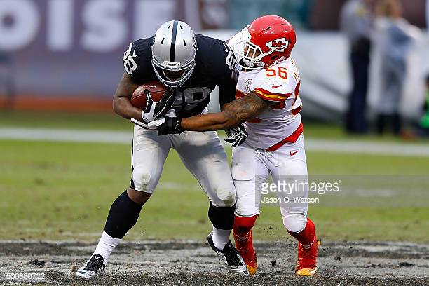 Tight end Clive Walford of the Oakland Raiders is tackled by inside linebacker Derrick Johnson of the Kansas City Chiefs during the third quarter at...