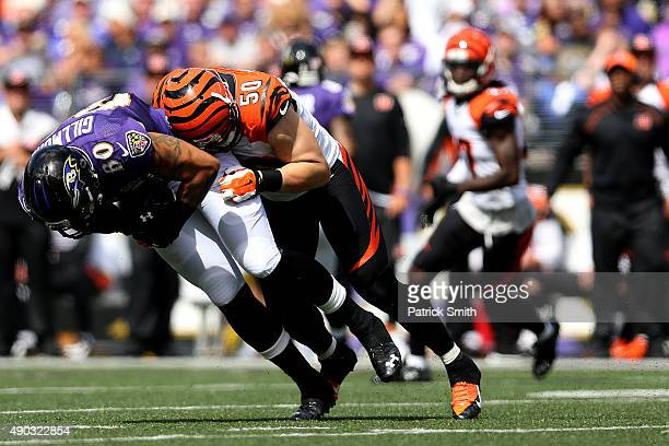 Tight end Crockett Gillmore of the Baltimore Ravens is tackled by outside linebacker AJ Hawk of the Cincinnati Bengals in the first quarter of a game...