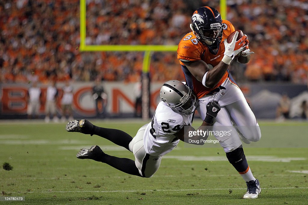 Tight end Daniel Fells #86 of the Denver Broncos runs the ball as Michael Huff #24 of the Oakland Raiders goes for the tackle in the first quarter at Sports Authority Field at Mile High on September 12, 2011 in Denver, Colorado.
