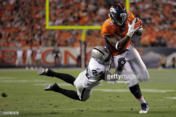 Tight end Daniel Fells of the Denver Broncos runs the ball as Michael Huff of the Oakland Raiders goes for the tackle in the first quarter at Sports...