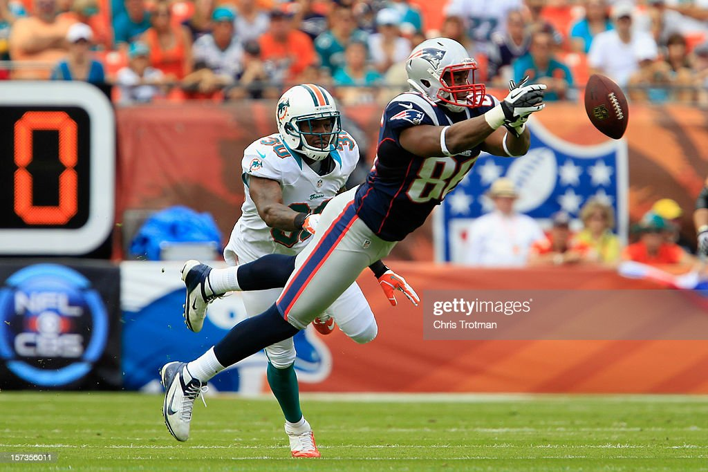 Tight end Daniel Fells #86 of the New England Patriots misses a catch as strong safety Chris Clemons #30 of the Miami Dolphins looks on at Sun Life Stadium on December 2, 2012 in Miami Gardens, Florida.