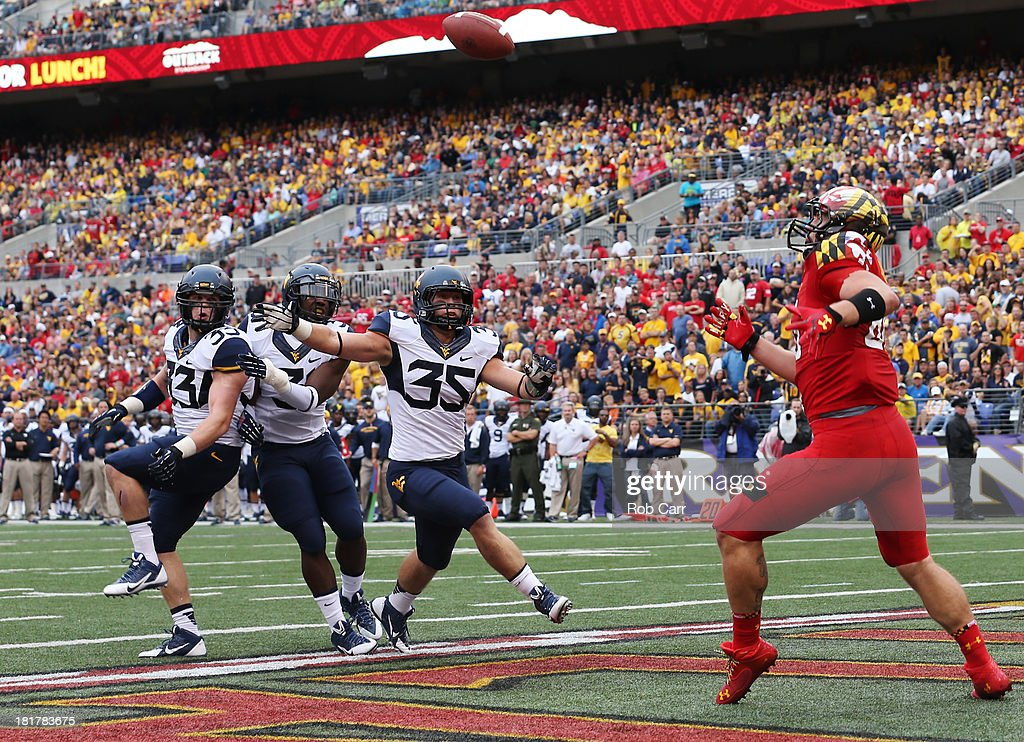 Tight end Dave Stinebaugh #86 of the Maryland Terrapins catches a tipped ball for a touchdown pass in front of linebacker Nick Kwiatkoski #35 of the West Virginia Mountaineers during the first half at M&T Bank Stadium on September 21, 2013 in Baltimore, Maryland.