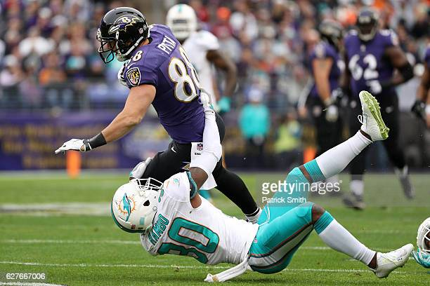 Tight end Dennis Pitta of the Baltimore Ravens carries the ball against free safety Bacarri Rambo of the Miami Dolphins in the first quarter at MT...