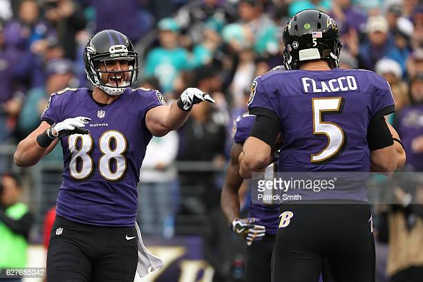 Tight end Dennis Pitta of the Baltimore Ravens celebrates with teammate quarterback Joe Flacco after scoring a second quarter touchdown against the...