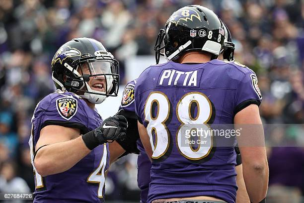 Tight end Dennis Pitta of the Baltimore Ravens celebrates with teammate fullback Kyle Juszczyk after scoring a second quarter touchdown against the...