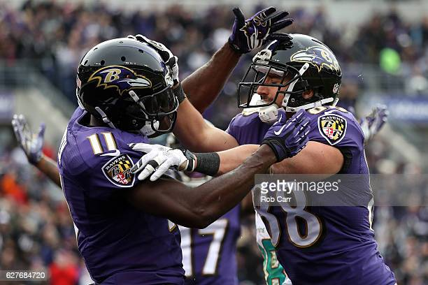 Tight end Dennis Pitta of the Baltimore Ravens celebrates with teammate wide receiver Kamar Aiken after scoring a second quarter touchdown against...