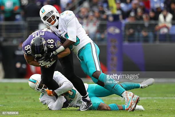 Tight end Dennis Pitta of the Baltimore Ravens is tackled by cornerback Bobby McCain and free safety Bacarri Rambo of the Miami Dolphins in the...