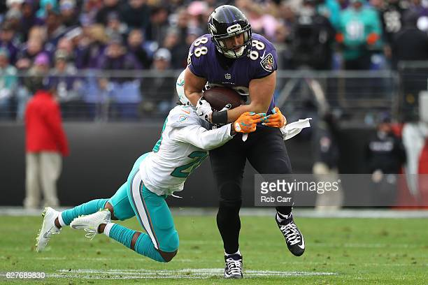 Tight end Dennis Pitta of the Baltimore Ravens is tackled by cornerback Bobby McCain of the Miami Dolphins in the second quarter at MT Bank Stadium...