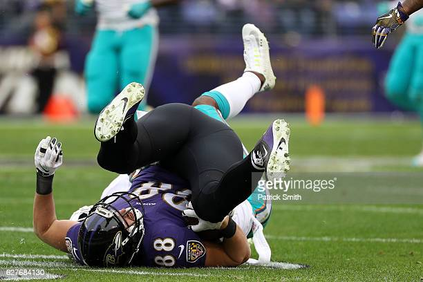 Tight end Dennis Pitta of the Baltimore Ravens is tackled by free safety Bacarri Rambo of the Miami Dolphins in the first quarter at MT Bank Stadium...