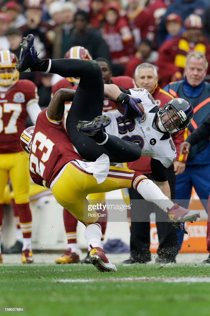 Tight end Dennis Pitta #88 of the Baltimore Ravens is tackled by cornerback DeAngelo Hall #23 of the Washington Redskins after catching a first half pass at FedExField on December 9, 2012 in Landover, Maryland.