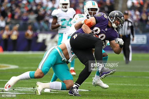Tight end Dennis Pitta of the Baltimore Ravens is tackled by middle linebacker Kiko Alonso of the Miami Dolphins in the first quarter at MT Bank...