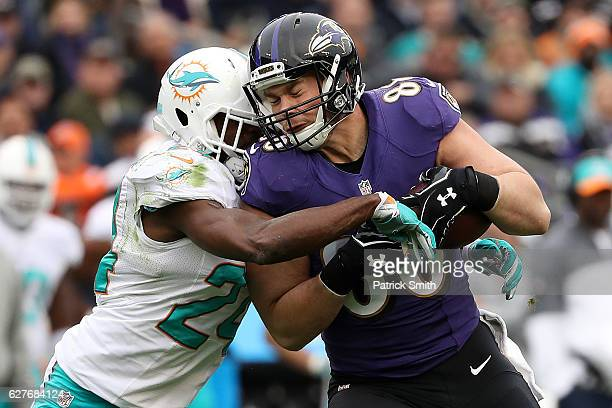 Tight end Dennis Pitta of the Baltimore Ravens is tackled by strong safety Isa AbdulQuddus of the Miami Dolphins in the first quarter at MT Bank...