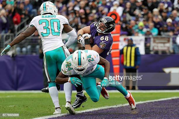 Tight end Dennis Pitta of the Baltimore Ravens scores a first quarter touchdown against strong safety Isa AbdulQuddus and free safety Bacarri Rambo...