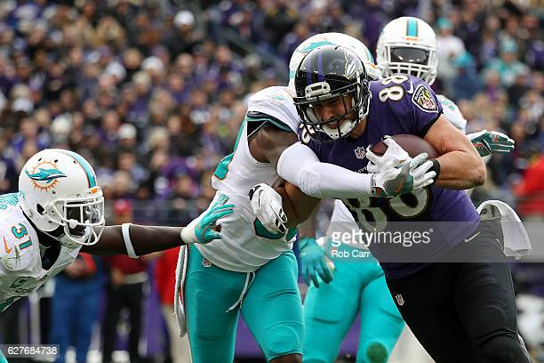 Tight end Dennis Pitta of the Baltimore Ravens scores a second quarter touchdown against free safety Michael Thomas free safety Bacarri Rambo and...