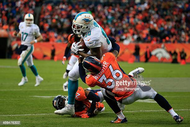 Tight end Dion Sims of the Miami Dolphins is tackled by cornerback Kayvon Webster of the Denver Broncos during a game at Sports Authority Field at...