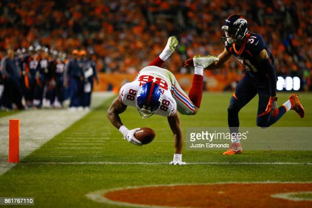 Tight end Evan Engram of the New York Giants dives into the end zone for a touchdown after beating strong safety Justin Simmons of the Denver Broncos...