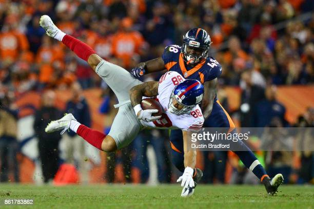 Tight end Evan Engram of the New York Giants flies through the air and is covered by outside linebacker Shaquil Barrett of the Denver Broncos at...