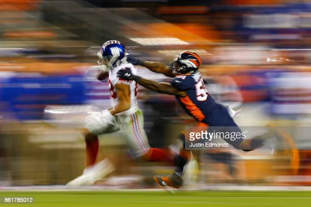 Tight end Evan Engram of the New York Giants runs towards the sidelines while being chased by Inside Linebacker Todd Davis of the Denver Broncos...