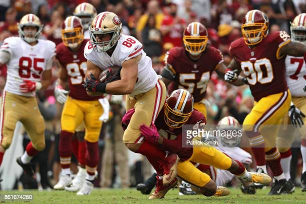 Tight end Garrett Celek of the San Francisco 49ers is tackled by cornerback Quinton Dunbar of the Washington Redskins during the first half at...