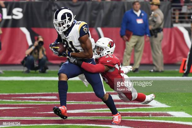 Tight end Gerald Everett of the Los Angeles Rams scores a first quarter touchdown over safety Budda Baker of the Arizona Cardinals during the NFL...