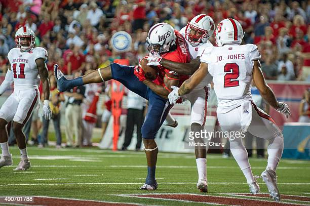 Tight end Gerald Everett of the South Alabama Jaguars catches a pass in front of safety Hakim Jones of the North Carolina State Wolfpack and safety...