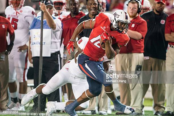 Tight end Gerald Everett of the South Alabama Jaguars looks to escape a tackle by linebacker Airius Moore of the North Carolina State Wolfpack on...