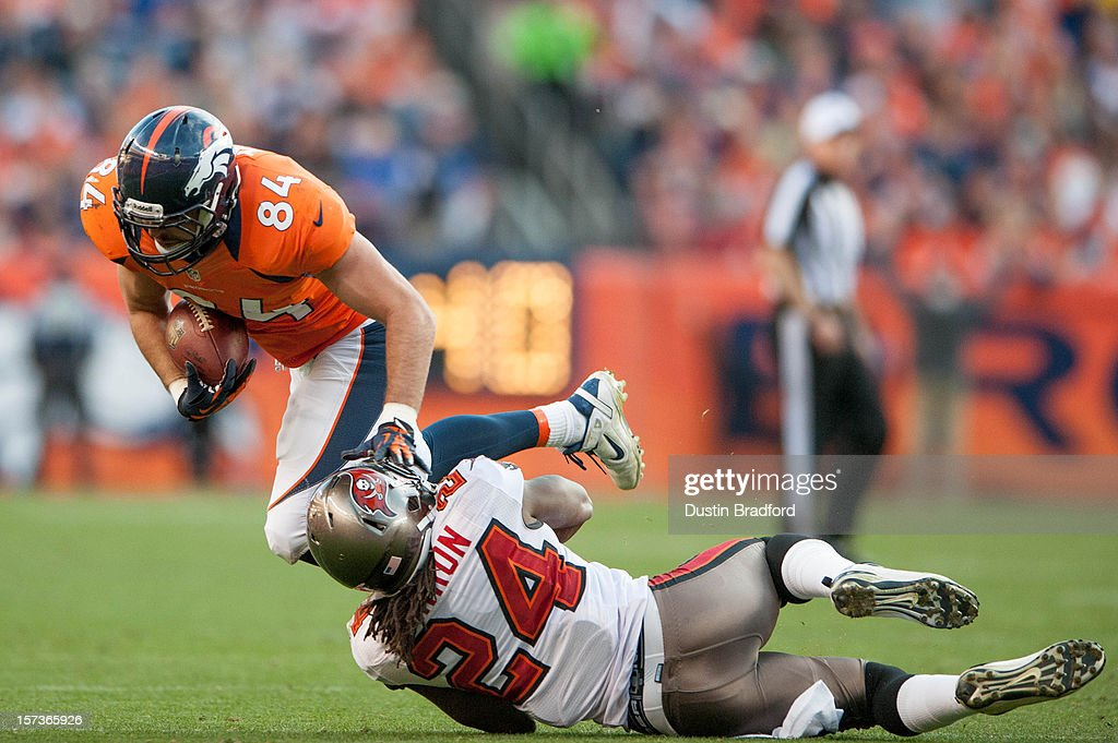 Tight end Jacob Tamme #84 of the Denver Broncos gains yardage after the catch as strong safety Mark Barron #24 of the Tampa Bay Buccaneers tackles him at Sports Authority Field Field at Mile High on December 2, 2012 in Denver, Colorado.