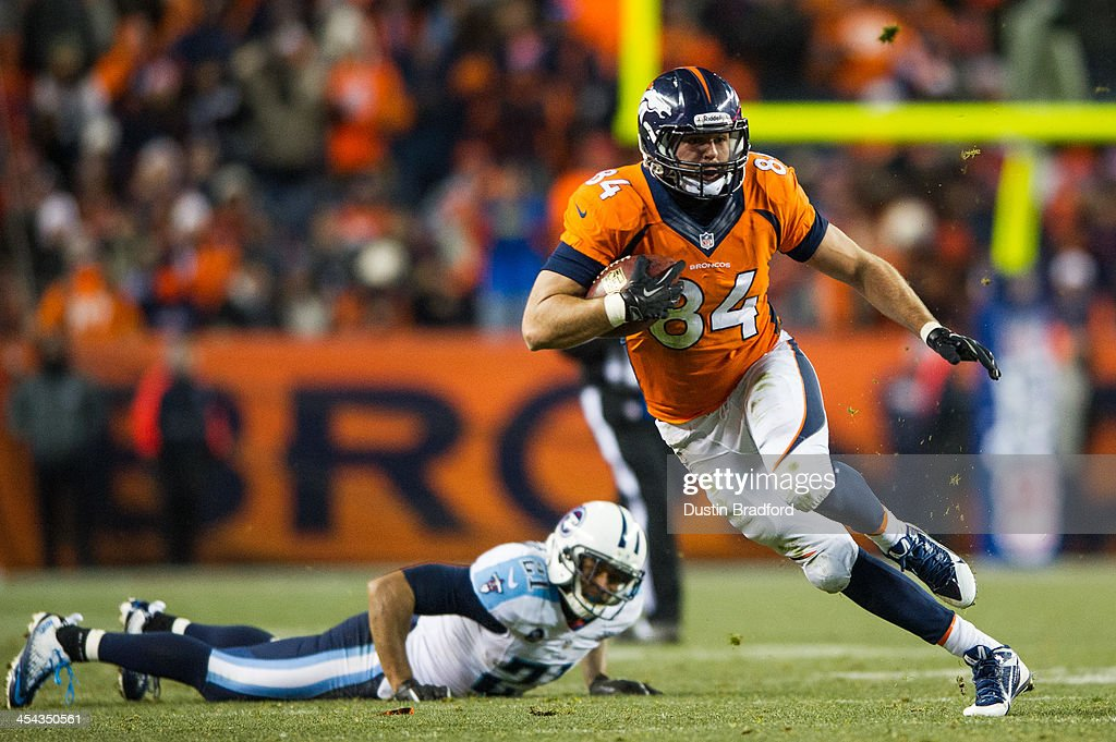 Tight end <a gi-track='captionPersonalityLinkClicked' href=/galleries/search?phrase=Jacob+Tamme&family=editorial&specificpeople=2128594 ng-click='$event.stopPropagation()'>Jacob Tamme</a> #84 of the Denver Broncos gains yards after the catch as free safety George Wilson #21 of the Tennessee Titans lies on the ground after missing a tackle at Sports Authority Field Field at Mile High on December 8, 2013 in Denver, Colorado.