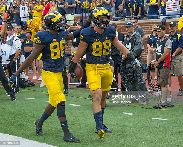 Tight end Jake Butt of the Michigan Wolverines celebrates his touchdown with teammate wide receiver Jehu Chesson during a college football game...